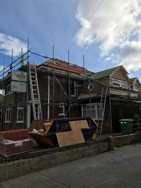 red brick house with scaffolding up for new roof
