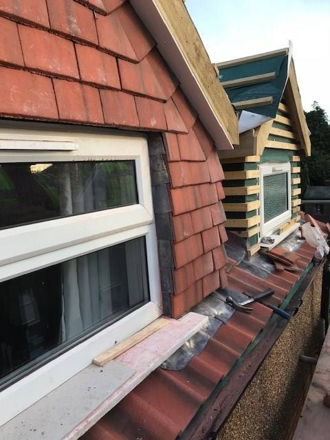 new tiles being put on red brick house